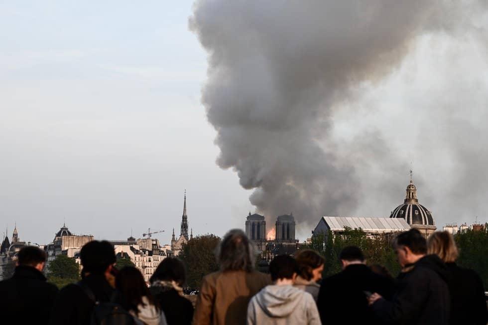 Una gran cantidad de humo, visible en estos momentos desde kilómetros de distancia, sale del edificio. En la imagen, la gente observa cómo el humo y las llamas se elevan sobre las torres de la catedral.