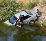 Rompen vidrio para salir de auto que cayó a canal